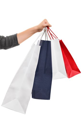 A close up shot of a female hand holding several colorful shopping bags, isolated on white background.