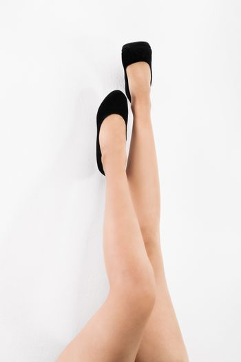 Naked female legs upside down with high heels, isolated on white background.