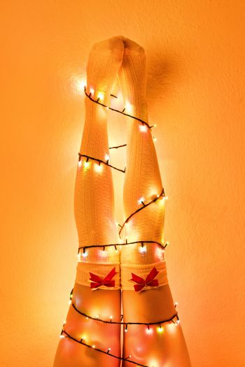 Female legs in white stockings with red bow ties wrapped with christmas lights.