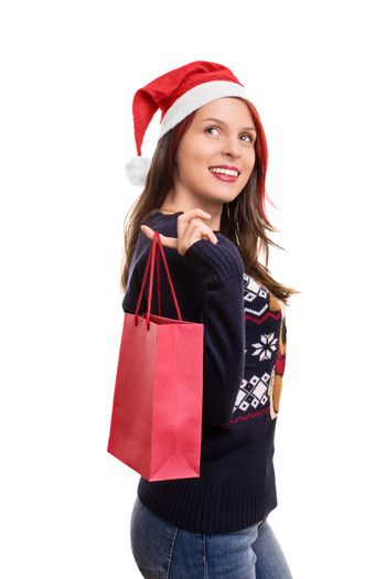 Holidays, shopping and presents. Beautiful young girl in winter clothes, wearing santa's hat, holding a shopping bag, isolated on white background.