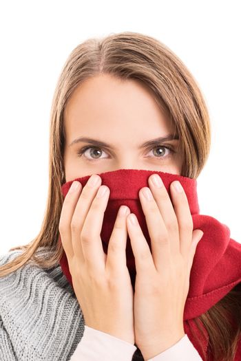 Close-up shot of a beautiful young girl in winter clothes, covering her mouth with a red scarf, isolated on white background.