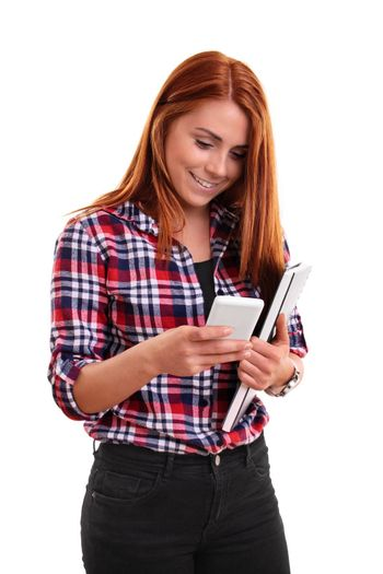 Beautiful smiling student girl holding a book and texting on her phone, isolated on white background. I have passed my exams!