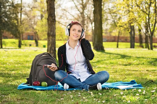 Beautiful young female student sitting on the grass in a park, listening to music, making a break from her studying.