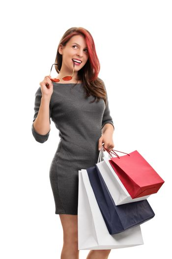 Girl in a shopping spree. A portrait of an excited beautiful young girl in a dress, holding a lot of shopping bags, isolated on white background. Girl thinking what to buy next.