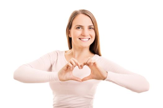 Beauty portrait of a smiling young girl making a heart shaped hand gesture, isolated on white background.
