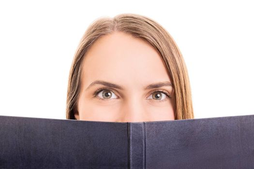 Close-up shot of a young girl making hiding behind her book, isolated on white background.