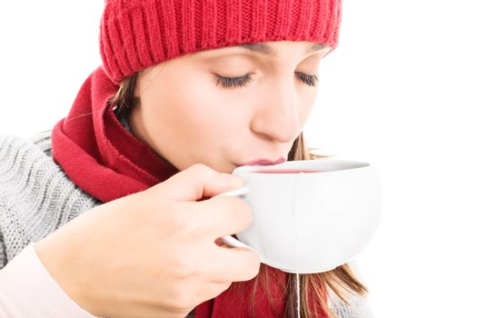 Close-up shot of a young girl wearing winter clothes and drinking a cup of hot drink, isolated on white background.
