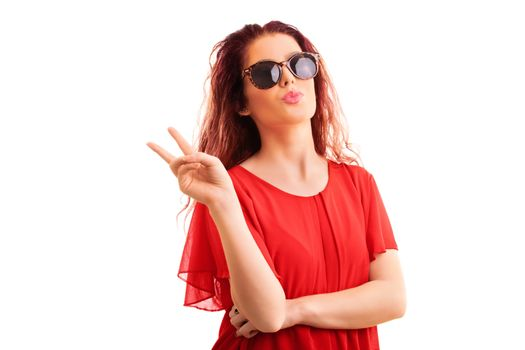 Young beautiful redhead girl in a red blouse with sunglasses gesturing the peace sign and sending a kiss, isolated on a white background.