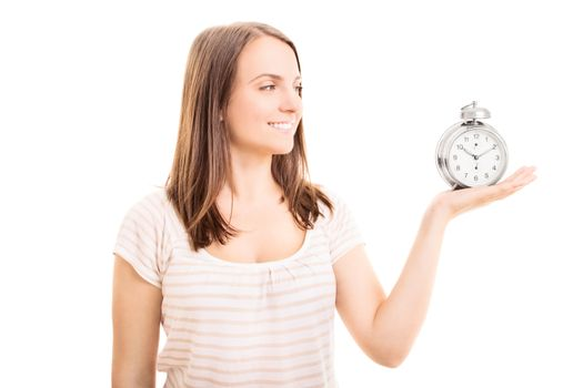 Beautiful young girl holding an old-fashioned alarm clock leaving an impression that it's time for something, isolated on white background.
