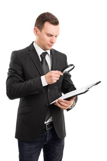 A portrait of a young businessman looking at a document on a clipboard through a magnifying glass, isolated on white background.