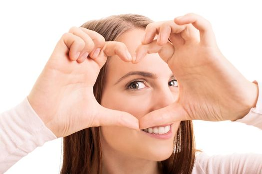 Close up beauty portrait of a smiling young girl looking through a heart shaped hands, isolated on white background.
