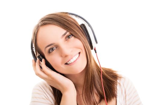 A portrait of a smiling young girl with headphones listening to music, isolated on white background.