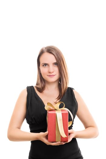 Beautiful young woman holding a lovely wrapped gift with a seductive smile, isolated on white background.