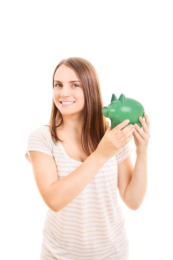 Beautiful young student girl holding a piggy bank, isolated on white background.
