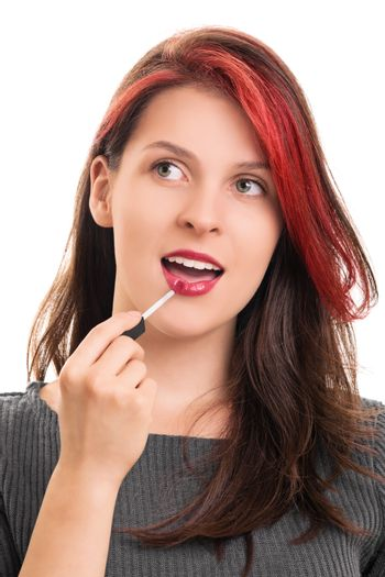A portrait of a young beautiful girl putting lipstick, isolated on white background.