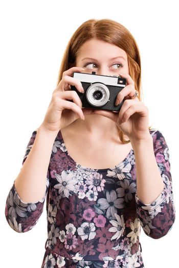 A portrait of a beautiful young girl holding a vintage camera, isolated on white background.