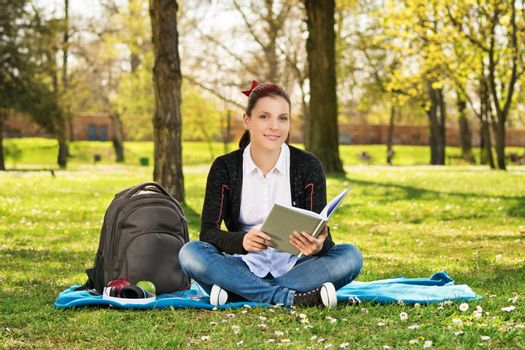 A portrait of a beautiful young female student holding a book, sitting on the grass in a park.