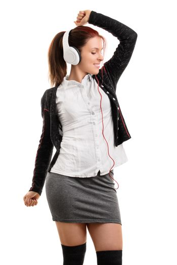Beautiful student girl in school uniform with headphones, listening to music and dancing, isolated on white background.