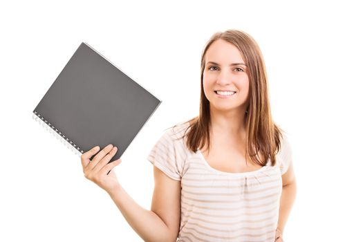 Smiling young student girl holding a notebook, isolated on white background.