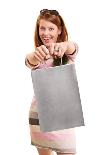 A portrait of a beautiful smiling girl, holding a shopping bag in front of her, isolated on white background.
