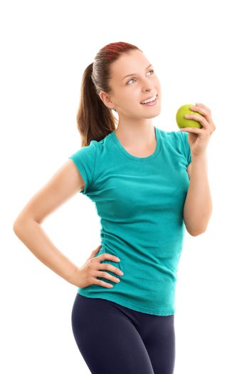 A portrait of a smiling beautiful young girl in fitness clothes holding an apple, isolated on white background.