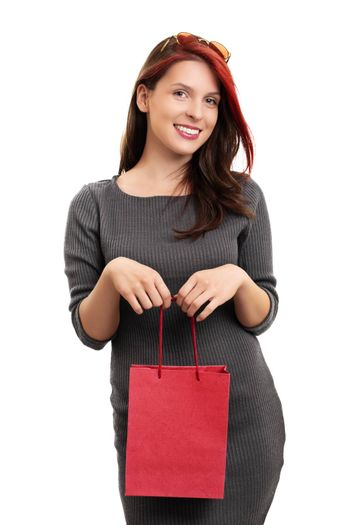 A portrait of a beautiful smiling young girl in a dress, holding a shopping bag, isolated on white background.
