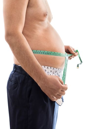 Close up of a young male with weight problems, measuring his big stomach with a measuring tape, isolated on white background.