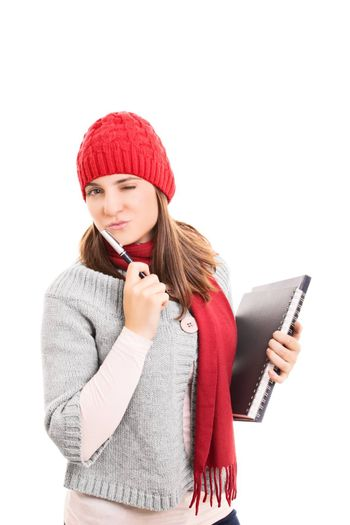 Portrait of a beautiful young woman winking, holding a pen, book and a notebook, wearing winter clothes. isolated on white background.