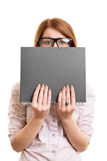 A portrait of a worried female student hiding behind her book, isolated on white background.
