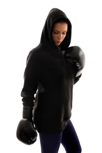 Young beautiful female boxer dressed in black looking down, with a dramatic light, isolated on a white background.