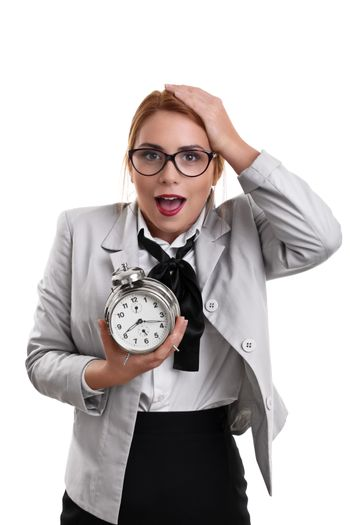 Beautiful young business woman dressed in a suit holding a clock with shocked expression, isolated on a white background.
