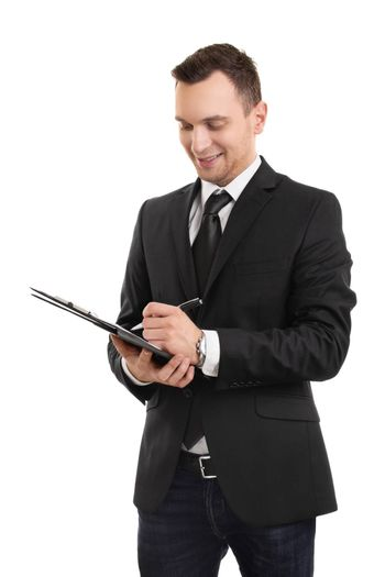 A portrait of a young businessman dressed in business casual clothes, writing on a clipboard, isolated on white background.
