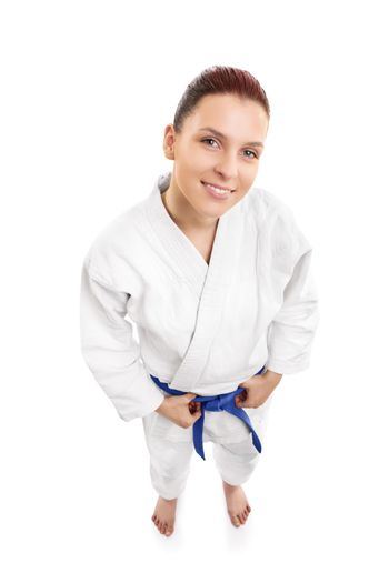 A portrait of a beautiful young female aikido fighter smiling, from top, isolated on white background.