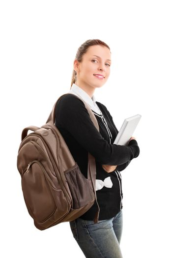 A portrait of a young female student with a backpack holding a book, isolated on white background.