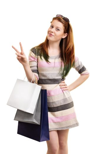 Beautiful young girl holding shopping bags and making a peace sign, isolated on a white background.