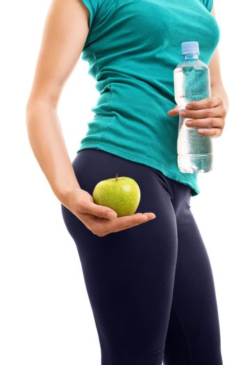 Healthy lifestyle's the key for fit figure. Fit girl holding a bottle of water and an apple, isolated on white background.