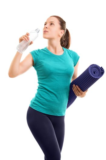 Portrait of a beautiful young girl holding an exercise mat and drinking water from a bottle, isolated on white background.