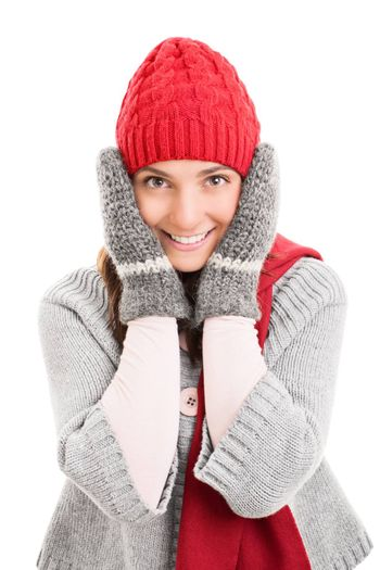 Portrait of a beautiful smiling young woman with warm winter clothes holding her cheeks, isolated on white background.