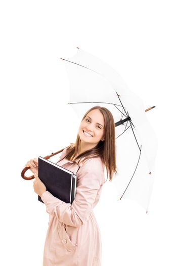Young girl under an umbrella holding some books, isolated on white background.