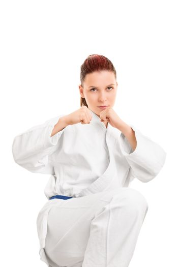 A portrait of a beautiful young beautiful girl in a kimono with blue belt, in a combat stance preparing for a kick, isolated on white background.