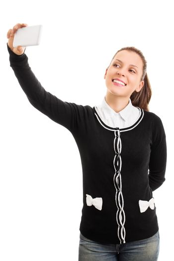 Young girl wearing school uniform and making a selfie, isolated on a white background.