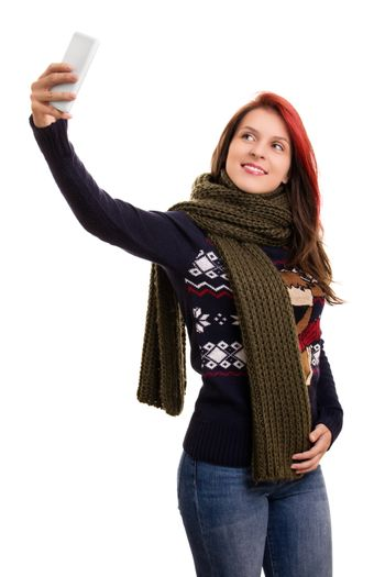 A portrait of a beautiful young girl in winter clothes taking a selfie, isolated on white background.