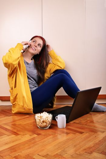 Young beautiful girl sitting on the floor in the bedroom in front of a laptop, preparing to watch a movie with popcorn and cup of coffee, talking on the phone.