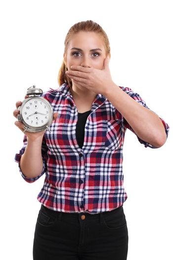 Portrait of a young beautiful woman dressed in plaid shirt holding an old school alarm clock, shocked and surprised to see what's the time. Isolated on a white background.