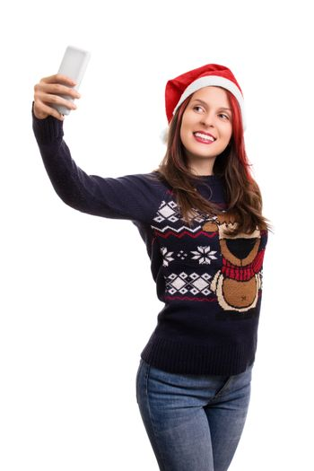 Young beautiful girl wearing a christmas hat taking a selfie, isolated on white background.