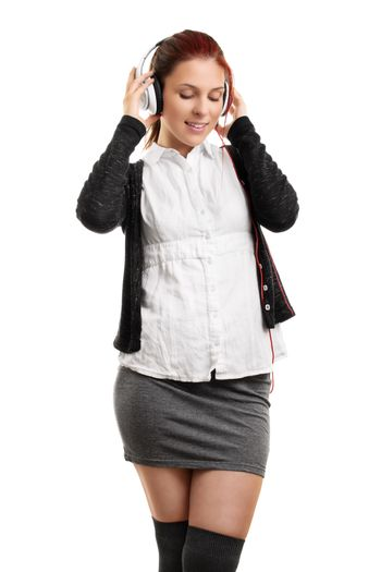 Portrait of a young beautiful woman enjoying music on her headphones, isolated on a white background.