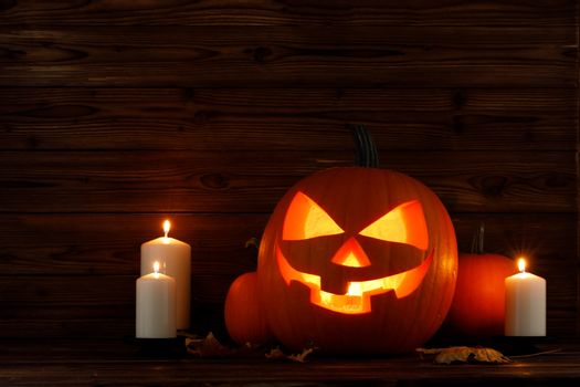 Halloween pumpkin head jack o lantern candles and dry maple leaves on wooden background