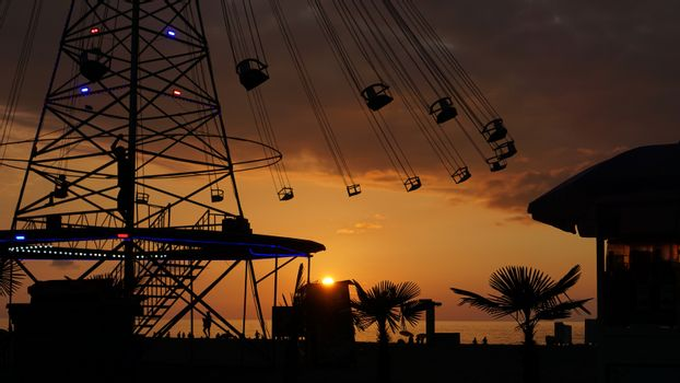 Swinging carousel roundabout chain ride at sunset