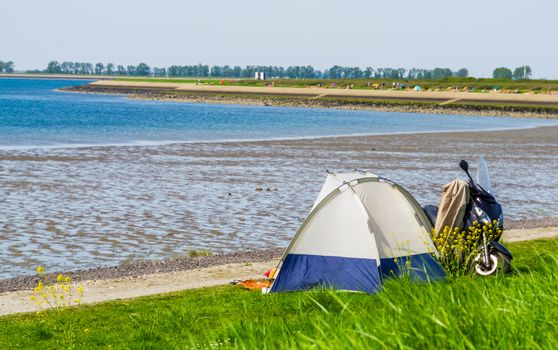 tourist camping in a tent at the beach of tholen, touristic location in zeeland, the netherlands