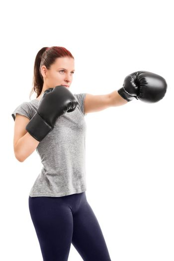 A portrait of a young beautiful girl with boxing gloves punching, isolated on white background.